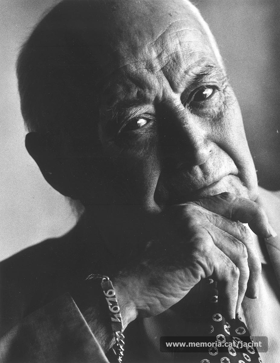 """1998. Jacint Carrió duent al canell el braçalet amb el número que tenia com a deportat a Mauthausen, el 4.676. Carrió duia sempre el braçalet com a testimoni del sofriment que, sota aquella xifra, havia patit al camp d'extermini nazi. (""""El Pou de les Lletres"""". Autor: Marc Vila Puig)"""